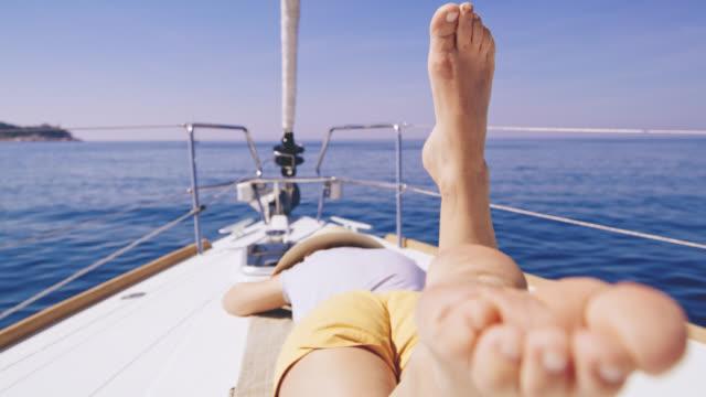vidéos et rushes de woman ms s'amuser se trouvant sur le pont d'un voilier - paradis