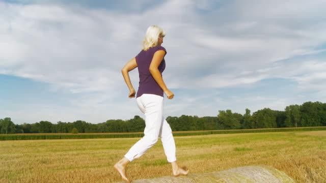 hd costante scatto: donna che si diverte su fieno bales - lanci e salti femminile video stock e b–roll