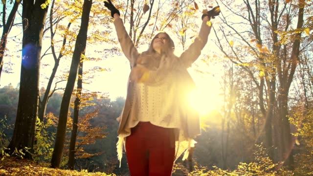 SLO MO Frau Spaß im Herbst Blätter verstreuten