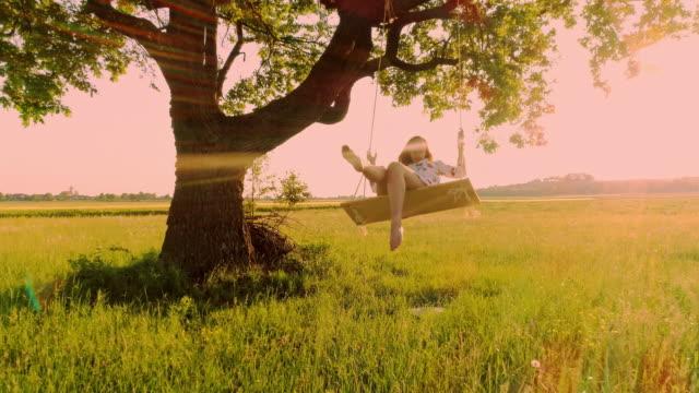 slo mo aerial woman having fun swinging at sunset - rope swing stock videos & royalty-free footage