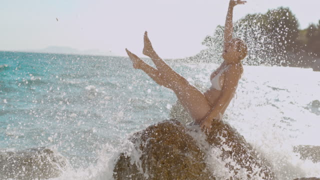 super slo mo woman having fun when the wave hit the rock and spray her - 1 minute or greater stock videos & royalty-free footage