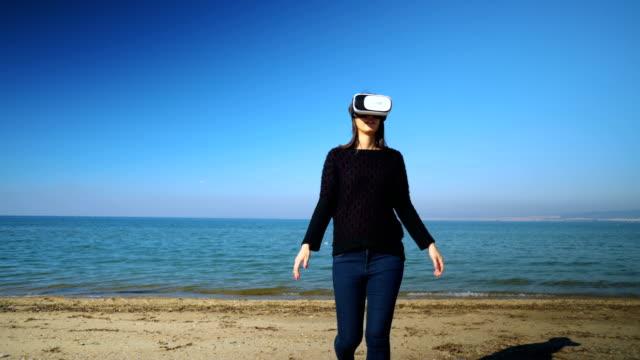 stockvideo's en b-roll-footage met vrouw plezier met een vr bril op het strand - de volgende stap