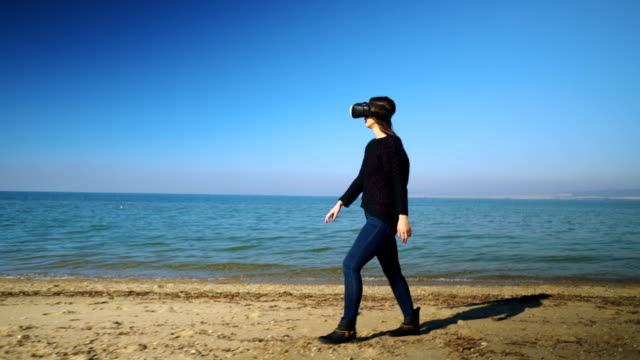 Woman having fun with VR glasses on the beach