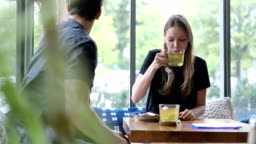 Woman having green tea while talking to friend in cafe