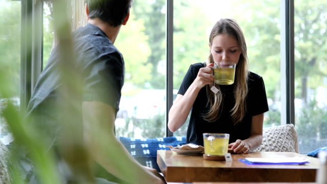 woman having green tea while talking to friend in cafe - refreshment stock videos & royalty-free footage