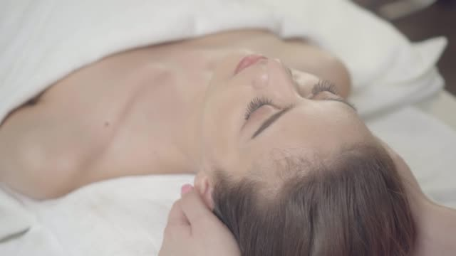 woman having head massage at spa - facial massage stock videos and b-roll footage