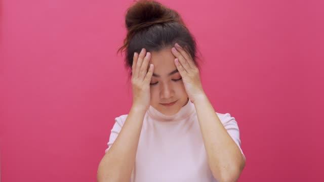vídeos y material grabado en eventos de stock de mujer que tiene dolor de cabeza sobre fondo rosa aislado 4k - mareado