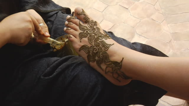 ms woman having henna designs applied to her foot/ morocco - squirting woman stock videos and b-roll footage