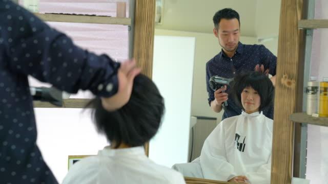 サロンで美容師で乾燥した彼女の髪のブローを持つ女性 - ヘアケア点の映像素材/bロール