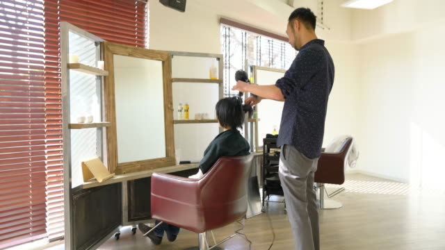 woman having her hair blow dried by a hairdresser in a salon - beauty salon stock videos & royalty-free footage