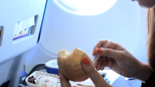 vídeos de stock, filmes e b-roll de mulher tendo um almoço no avião - comida e bebida