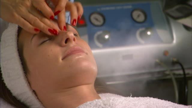 cu, woman having steam treatment and face massage - タオルにくるまる点の映像素材/bロール