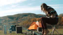 Woman having stomachache on camping trip by the lake
