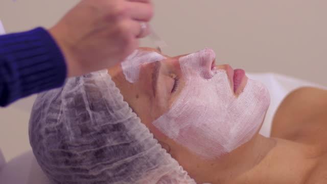 vídeos de stock, filmes e b-roll de mulher com máscara cosmética facial branca no salão spa - moisturiser