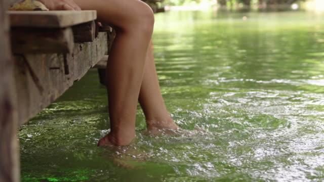 vídeos y material grabado en eventos de stock de mujer que feliz y sentado en un muelle de madera y cuelgan los pies en el agua - embarcadero
