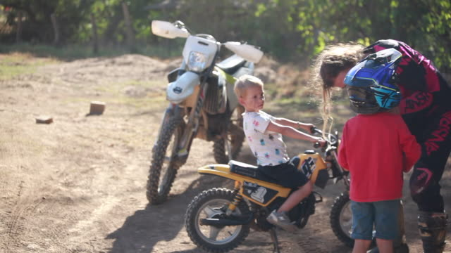 a woman helping a young boy with the strap on his dirt bike helmet and take sit off while another young boy is on dirt bike behind them rocking it back and forth - kelly mason videos stock videos & royalty-free footage