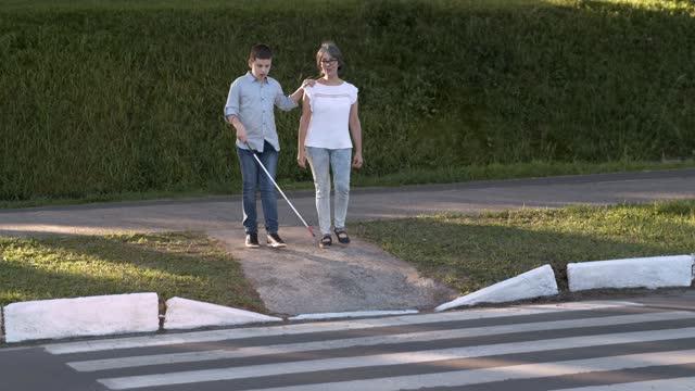 vídeos y material grabado en eventos de stock de mujer ayudando a niño ciego a cruzar la calle - cruce