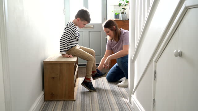 woman helping boy put shoes on - footwear stock videos & royalty-free footage
