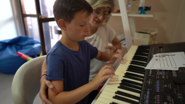 woman helping little boy with playing synthesizer during music therapy at rehabilitation center - invisible disability stock videos & royalty-free footage
