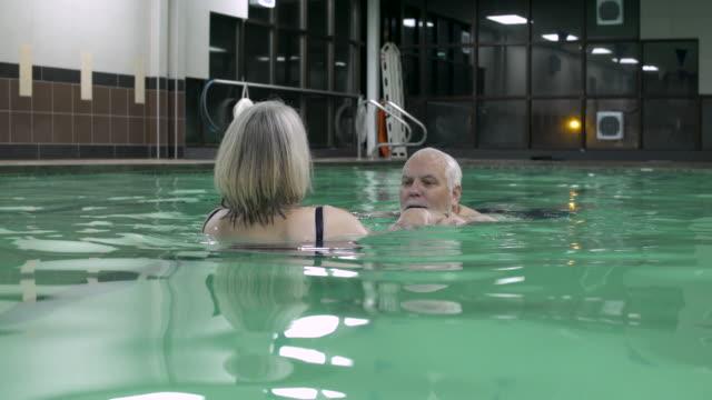 vídeos y material grabado en eventos de stock de woman helping man swim in swimming pool. - 50 59 años