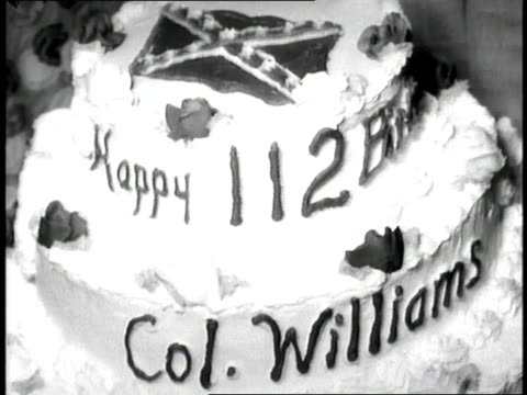 a woman helps a civil war veteran cut into his cake for his 112th birthday - confederate flag stock videos & royalty-free footage