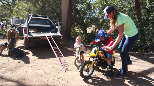 a woman helps a young boy get on his dirt bike while another young boy rides a wooden bike behind a pickup truck on a hot summer day - kelly mason videos stock videos & royalty-free footage