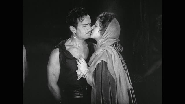Woman helps captured man (Douglas Fairbanks) by passing a knife with a kiss