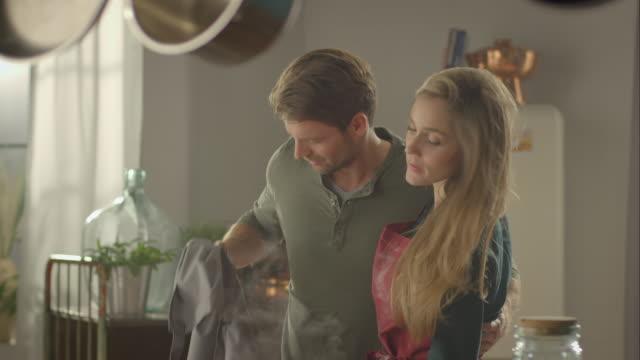 donna aiuta l'uomo indossare un grembiule - cooking pan video stock e b–roll
