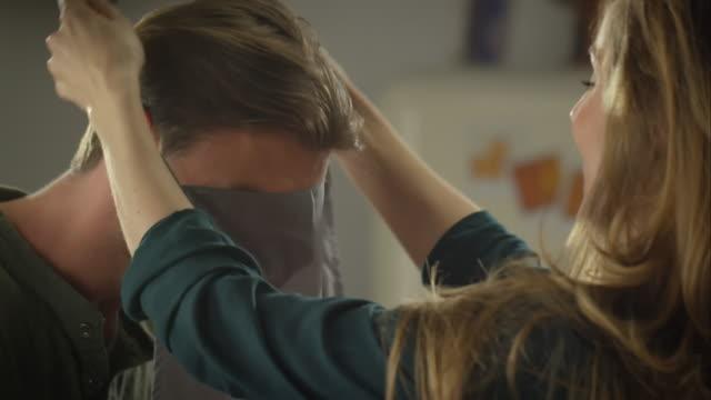 vídeos y material grabado en eventos de stock de hombre mujer ayudan a poner en delantal - delantal