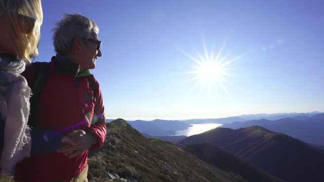woman helps up man onto a rock on top of a mountain looking in the distance - standing stock videos & royalty-free footage