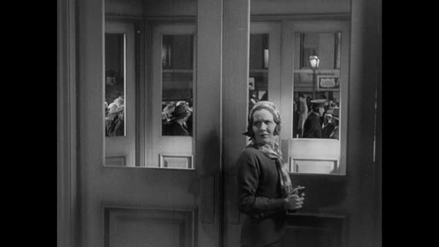 1931 woman hesitates before walking out of front glass doors onto busy city street - 1931 stock-videos und b-roll-filmmaterial