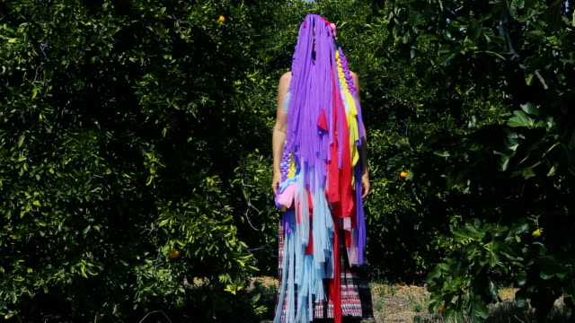 Woman Hiding Behind Colorful Fringe Mask in Orange Orchard