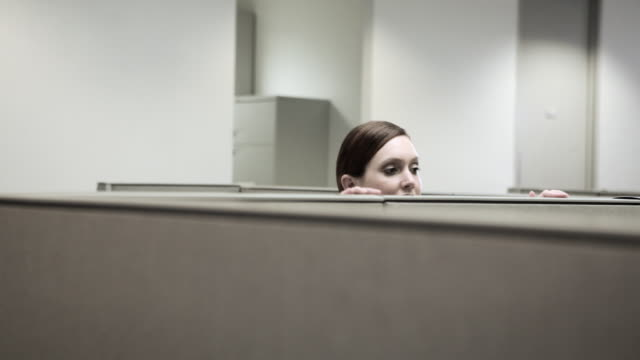 woman hiding behind cubicle in office - 隠れる点の映像素材/bロール