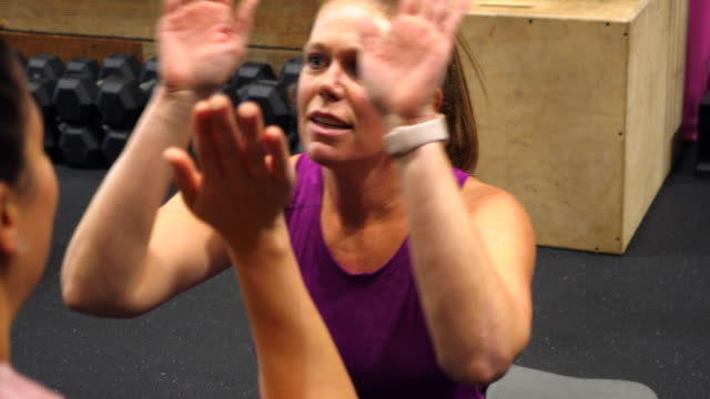 vidéos et rushes de ms woman high fiving workout partner while doing sit-ups in gym - enjoyment