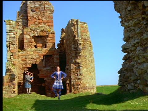 woman highland dancing + man playing bagpipes near castle ruins / newark castle, scotland - kilt stock videos & royalty-free footage