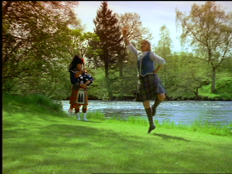 woman highland dancing + man playing bagpipes on grass near river / callander, scotland - スコットランド点の映像素材/bロール