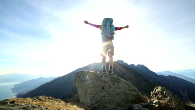 woman hiker arms outstretched on mountain ridge crest - mountain peak stock videos and b-roll footage