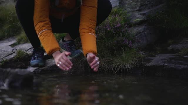 vídeos y material grabado en eventos de stock de mujer excursionista bebe agua dulce del arroyo en la naturaleza - manos ahuecadas