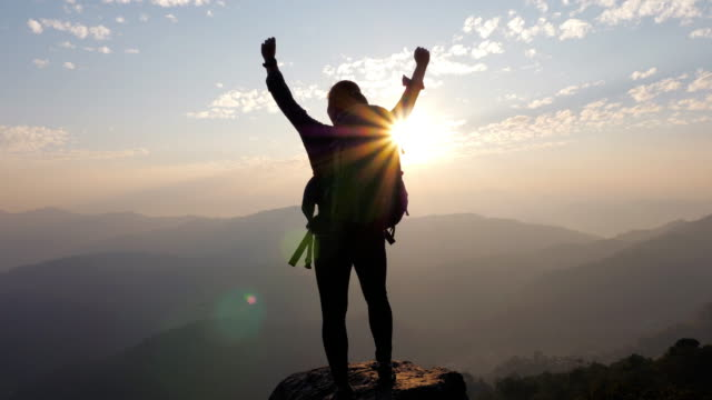 woman hiker hiking on the top of the mountain and hands up on head celebrating successful , slow motion - cliff stock videos & royalty-free footage