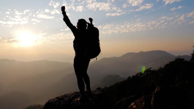 vídeos de stock, filmes e b-roll de caminhante da mulher que caminha na parte superior da montanha e as mãos acima na cabeça que comemora bem sucedida, slow motion - coragem