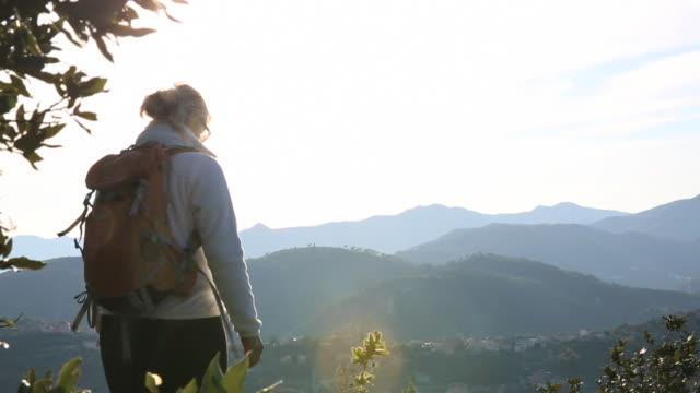 woman hiker pauses on ridge above distant hills - solo una donna di età media video stock e b–roll