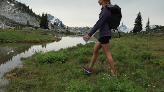 stockvideo's en b-roll-footage met woman hiker reaches pristine high alpine lake on moody day - haar naar achteren