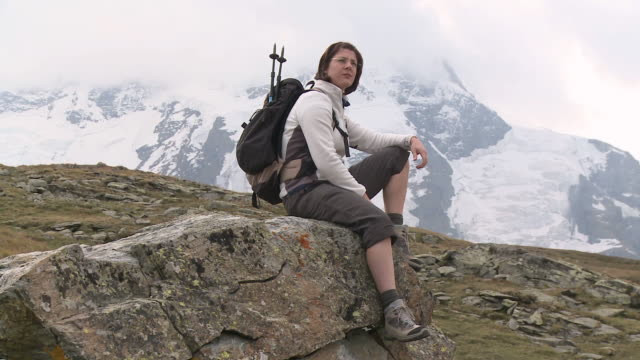 vídeos de stock, filmes e b-roll de ms woman hiker siting and taking rest on rock at riffelberg / zermatt, valais, switzerland - só uma mulher de idade mediana