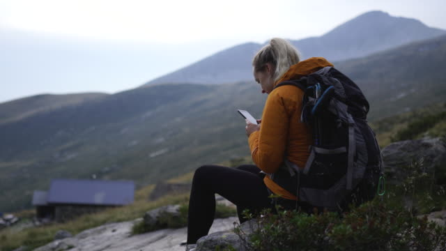 woman hiker sits on top of mountain in nature texting on smartphone - photographing stock videos & royalty-free footage