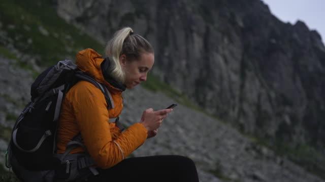 frau wanderer sitzt auf dem berg in der natur sms auf dem smartphone - blondes haar stock-videos und b-roll-filmmaterial