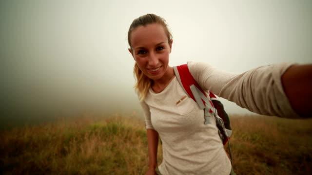 vídeos de stock e filmes b-roll de mulher caminhada toma selfie em prados de montanha - cultura jovem