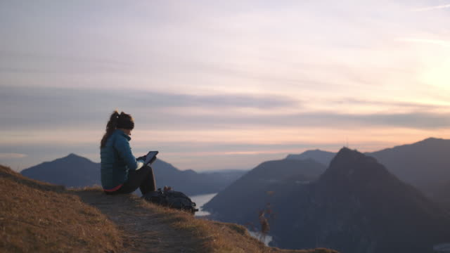 woman hiker works on digital tablet overlooking mountains and lake below - leggings stock videos & royalty-free footage