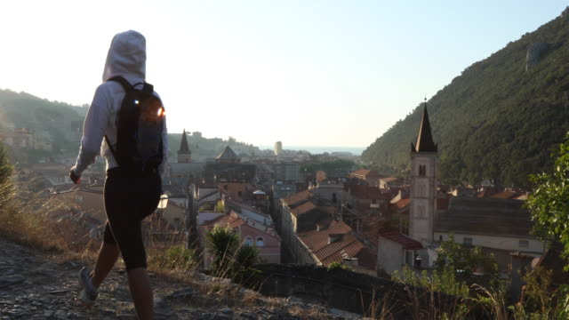 woman hikes along cobblestone path, above village - pedal pushers stock videos & royalty-free footage