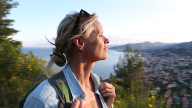 Woman hikes along path above village, sea, sunrise