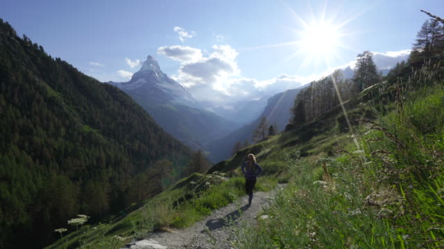 woman hikes alpine trail with sunset view of swiss matterhorn - only mid adult women stock videos & royalty-free footage